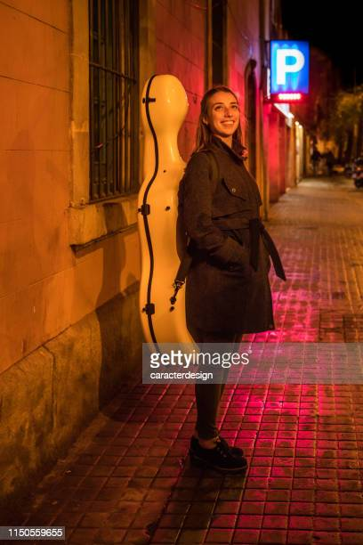 violoncellist at the street carrying instrument - cellist stock pictures, royalty-free photos & images