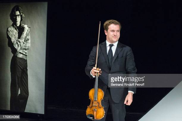 Violonist Renaud Capucon performs during a tribute to late fashion designer Yves Saint Laurent whose 1975 photo by Helmut Newton is seen at left at...