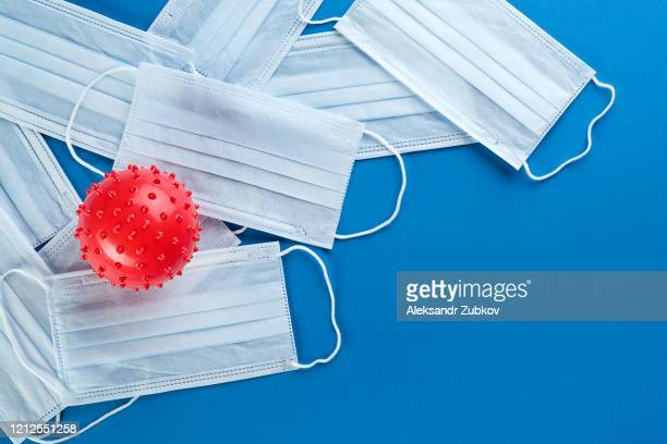 viral coronavirus bacteria and protective medical disposable masks on a blue background. concept of air pollution , pneumonia outbreaks, epidemics , and prevention of the risk of biological pollution. - mask stock pictures, royalty-free photos & images
