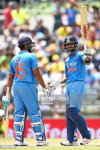 Virat Kholi of India raises his bat to celebrate his half century during the Victoria Bitter One Day International Series match between Australia and...