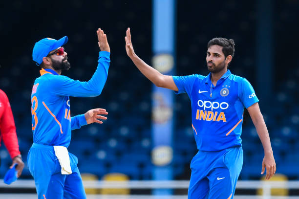 Virat Kohli and Bhuvneshwar Kumar of India celebrate the dismissal of Chris Gayle of West Indies during the 2nd ODI match between West Indies and...