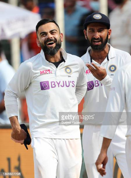 Virat Kohli and Cheteshwar Pujara of India celebrate victory after Day Three of the 4th Test Match between India and England at the Narendra Modi...