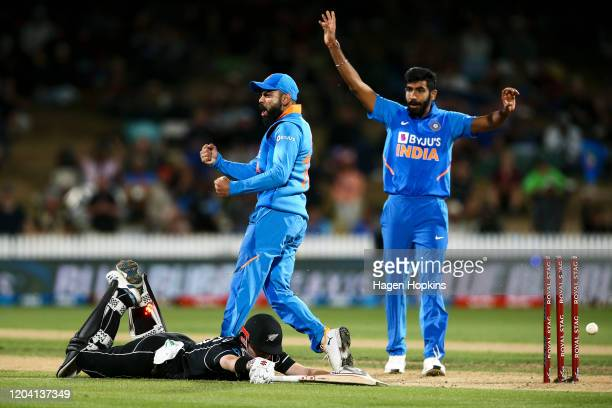 Virat Kohli and Jasprit Bumrah of India celebrate the wicket of Henry Nicholls of New Zealand during game one of the One Day International Series...