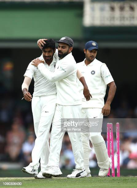 Virat Kohli and Jasprit Bumrah of India celebrates the wicket of Peter Handscomb of Australia during day four of the Fourth Test match in the series...