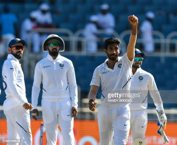 Virat Kohli and KL Rahul look on as Jasprit Bumrah of India shows the ball to supporters during day 2 of the 2nd Test between West Indies and India...