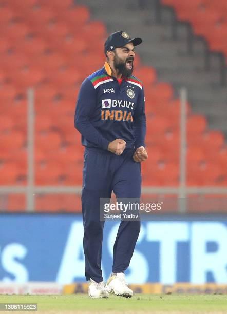 Virat Kohli celebrates the wicket of Jos Buttler, bowled by Bhuvneshwar Kumar and caught by Hardik Pandya during the 5th T20 International between...