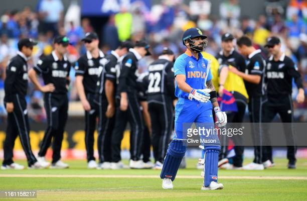 Virat Kohli, Indian Captain walks after being bowled lbw of the bowling of Trent Boult of New Zealand during resumption of the Semi-Final match of...