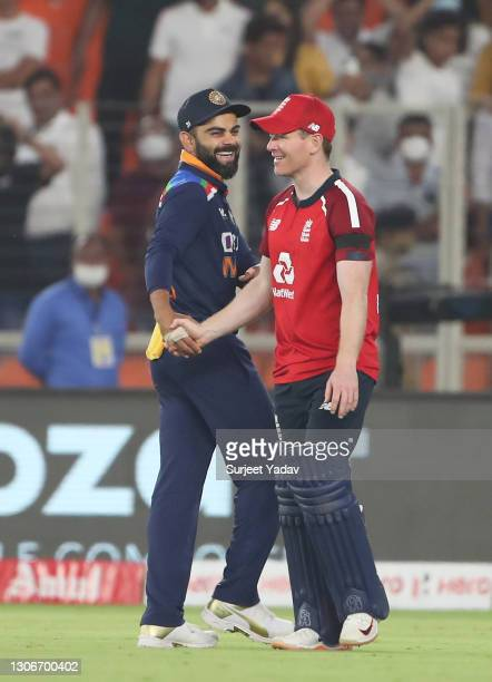 Virat Kohli of India and Eoin Morgan of England interact following the 1st T20 International match between India and England at Sardar Patel Stadium...