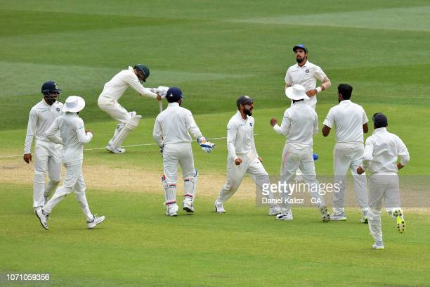 Virat Kohli of India and his team celebrate during day five of the First Test match in the series between Australia and India at Adelaide Oval on...
