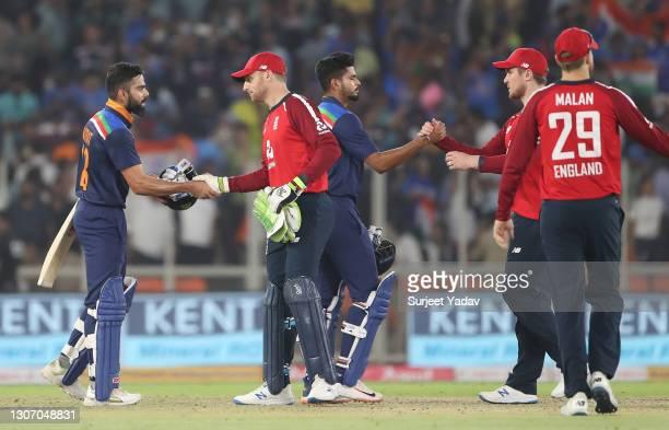Virat Kohli of India and Jos Buttler of England interact following the 2nd T20 International match between India and England at Narendra Modi Stadium...