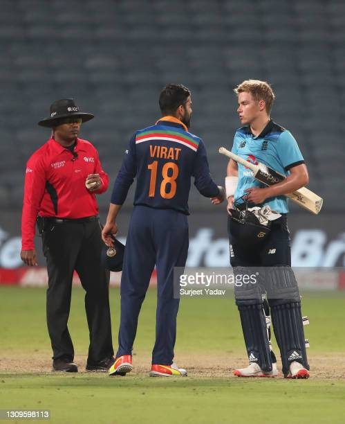Virat Kohli of India and Sam Curran of England interact following the 3rd One Day International match between India and England at MCA Stadium on...