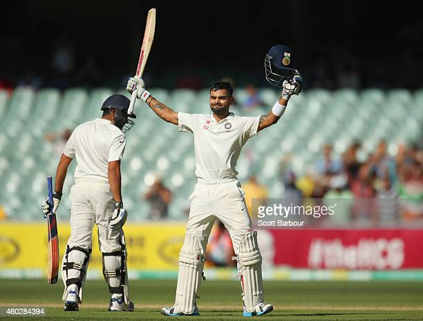 Virat Kohli of India celebrates as he reaches his century as Rohit Sharma looks on during day three of the First Test match between Australia and...