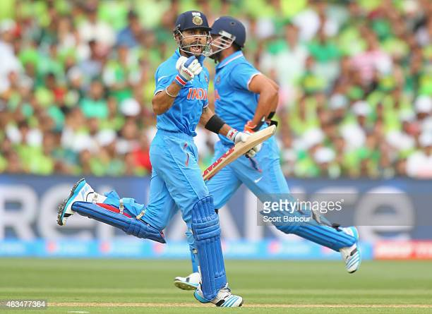 Virat Kohli of India celebrates as he reaches his century as Suresh Raina runs betweeen the wickets during the 2015 ICC Cricket World Cup match...