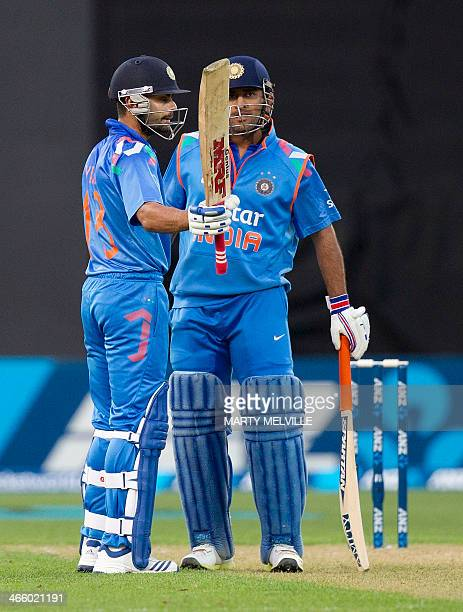 Virat Kohli of India celebrates his half century with team mate and captain MS Dhoni during the fifth and final international one day cricket match...
