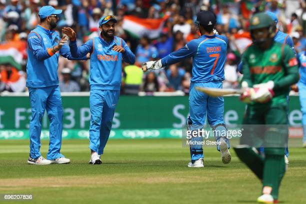 Virat Kohli of India celebrates taking a catch off the bowling of Kedar Jadhav to claim the wicket of Mushfiqur Rahim of Bangladesh during the ICC...