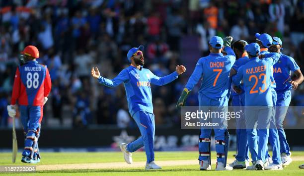 Virat Kohli of India celebrates the wicket of Mujeeb Ur Rahman of Afghanistan with his teammates during the Group Stage match of the ICC Cricket...