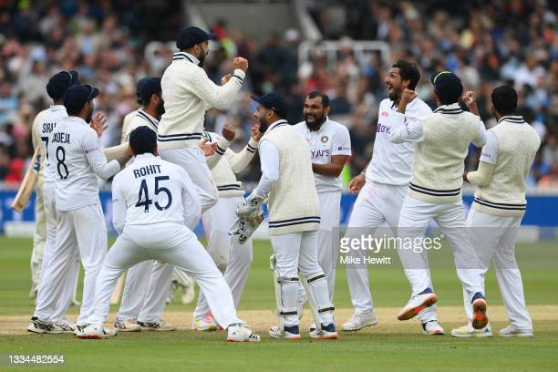 Virat Kohli of India celebrates with bowler Ishant Sharma and team mates after the successful review for lbw against Jonny Bairstow of England during...