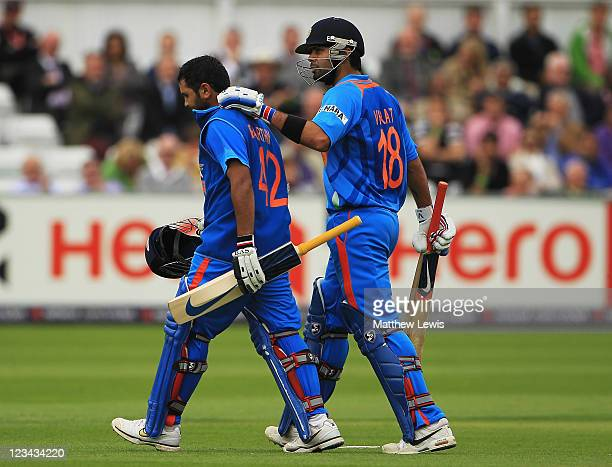 Virat Kohli of India consoles Parthiv Patel after he was caught by Craig Kieswetter of England off the bowling of James Anderson during the 1st...