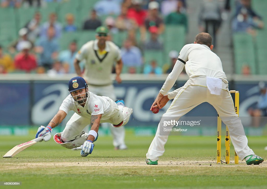Virat Kohli of India dives to make his ground as Nathan Lyon of Australia misses a run out opportunity during day five of the Third Test match between Australia and India at Melbourne Cricket Ground on December 30, 2014 in Melbourne, Australia.