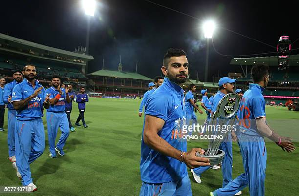 Virat Kohli of India does a honour lap with the team holding the T20 trophy after winning the third Twenty20 international cricket match between...