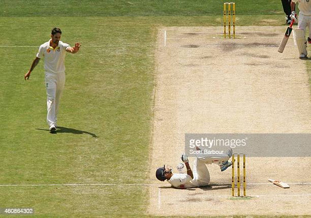 Virat Kohli of India falls to the ground after being hit by a throw at the stumps from bowler Mitchell Johnson of Australia during day three of the...