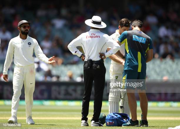 Virat Kohli of India has words with Tim Paine of Australia as he has a hand injury seen to during day five of the First Test match in the series...