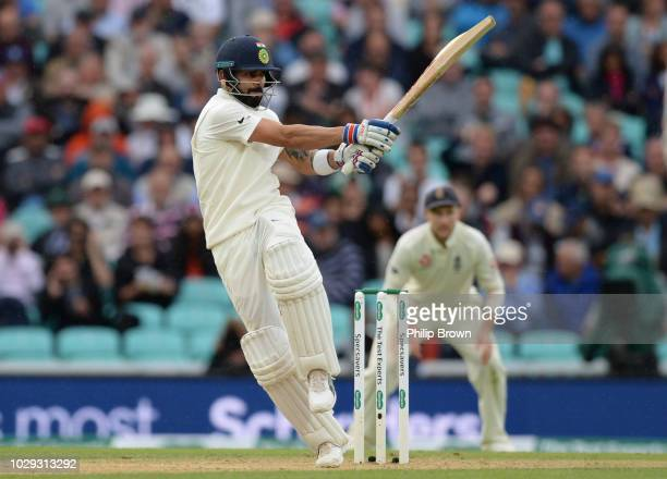 Virat Kohli of India hits a four watched by Joe Root of England during the fifth Specsavers Test Match between England and India at The Kia Oval on...