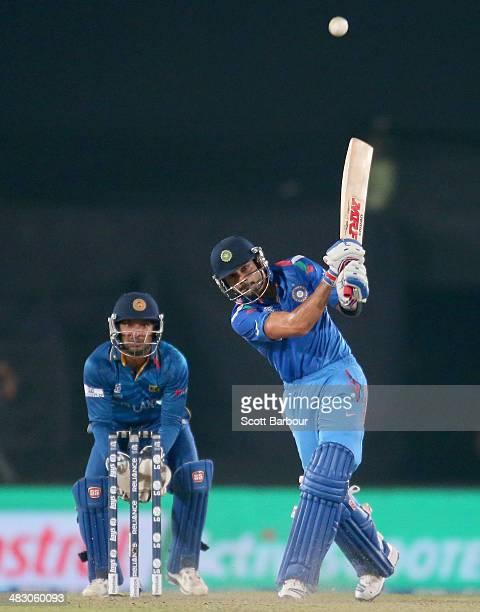 Virat Kohli of India hits a six as Kumar Sangakkara of Sri Lanka looks on during the Final of the ICC World Twenty20 Bangladesh 2014 between India...