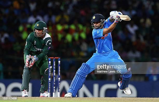 Virat Kohli of India hits the ball towards the boundary, as Kamran Akmal of Pakistan looks on during the ICC World Twenty20 2012 Super Eights Group 2...