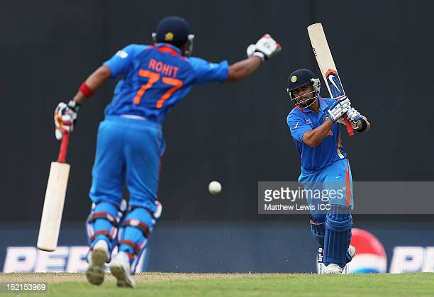Virat Kohli of India hits the ball towards the boundary as team mate Rohit Sharma moves out of the way during the ICC T20 World Cup warm up match...