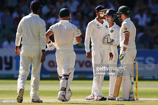 Virat Kohli of India is held back by keeper Wriddhiman Saha as he has words with Steve Smith of Australia after he padded away another ball from...