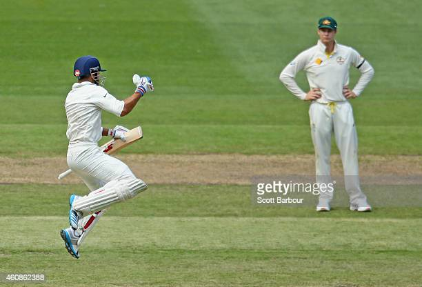 Virat Kohli of India leaps as he celebrates after reaching his century as Steven Smith of Australia looks on during day three of the Third Test match...