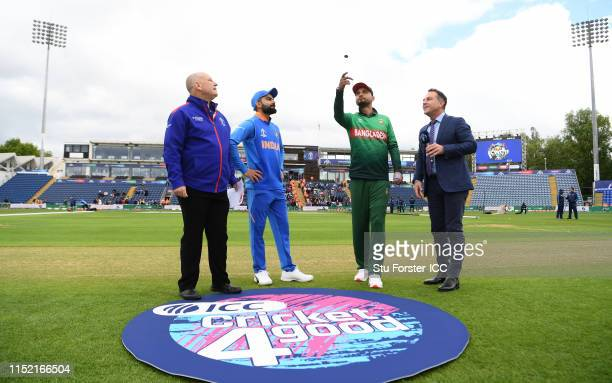 Virat Kohli of India looks on as Bangladesh captain Mashrafe Mortaza tosses the coin before the ICC Cricket World Cup 2019 Warm Up match between...