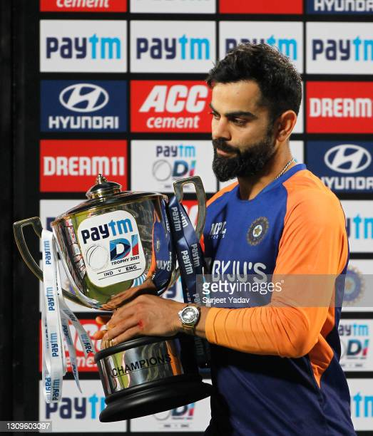 Virat Kohli of India looks on with the trophy following the 3rd One Day International match between India and England at MCA Stadium on March 28,...