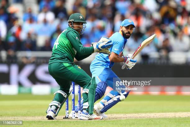 Virat Kohli of India plays to the offside as Pakistan wicktkeeper Sarfaraz Ahmed looks on during the Group Stage match of the ICC Cricket World Cup...