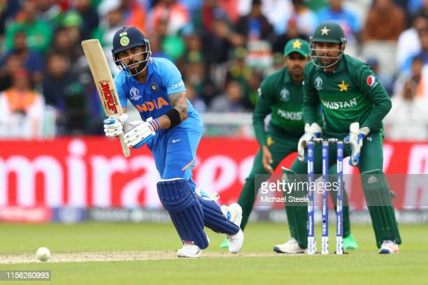 Virat Kohli of India plays to the onside as Pakistan wicktekeeper Sarfaraz Ahmed looks on during the Group Stage match of the ICC Cricket World Cup...