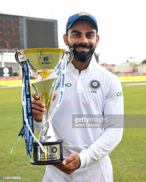Virat Kohli of India poses with the trophy after winning on day 4 of the 2nd and final Test between West Indies and India at Sabina Park Kingston...