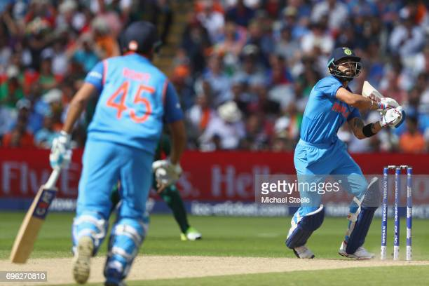 Virat Kohli of India pulls a delivery as Rohit Sharma backs up during the ICC Champions Trophy SemiFinal match between Bangladesh and India at...