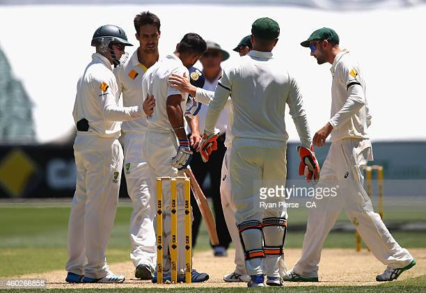 Virat Kohli of India removes his helmet after being struck by a bouncer bowled by Mitchell Johnson of Australia during day three of the First Test...