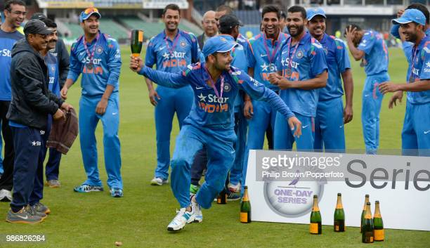 Virat Kohli of India runs about with a champagne bottle as India celebrate winning the Royal London One Day International series 31 following the 5th...