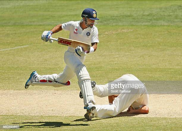 Virat Kohli of India runs between the wickets as bowler Ryan Harris of Australia falls over during day five of the First Test match between Australia...