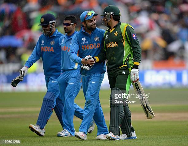 Virat Kohli of India shakes hands with Pakistan captain MisbahulHaq as rain stops play during the ICC Champions Trophy match between India and...