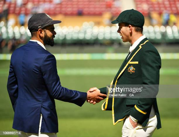 Virat Kohli of India shakes hands with Tim Paine of Australia at the coin toss during day one of the First Test match in the series between Australia...