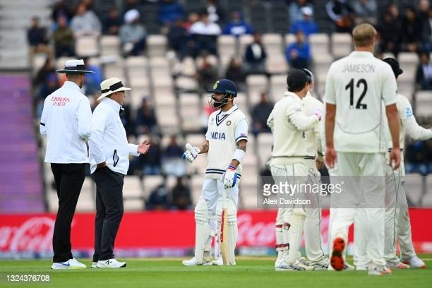 Virat Kohli of India talks to Umpires Richard Illingworth and Michael Gough after a Umpire review for his wicket during Day 2 of the ICC World Test...