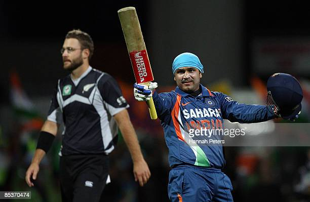 Virendar Sehwag of India celebrates his century as New Zealand captain Daniel Vettori looks on during the fourth one day international match between...