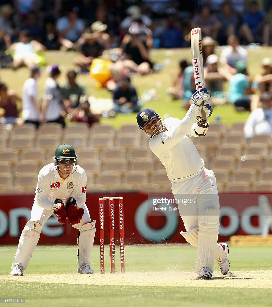 Virender Sehwag of India drives with Brad Haddin of Australia looking on during day four of the Fourth Test Match between Australia and India at Adelaide Oval on January 27, 2012 in Adelaide, Australia.