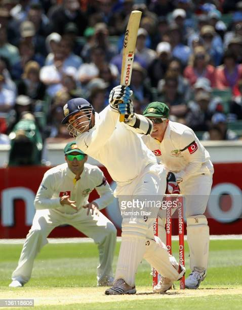 Virender Sehwag of India drives with Michael Clarke and Brad Haddin of Australia looking on during day two of the First Test match between Australia...