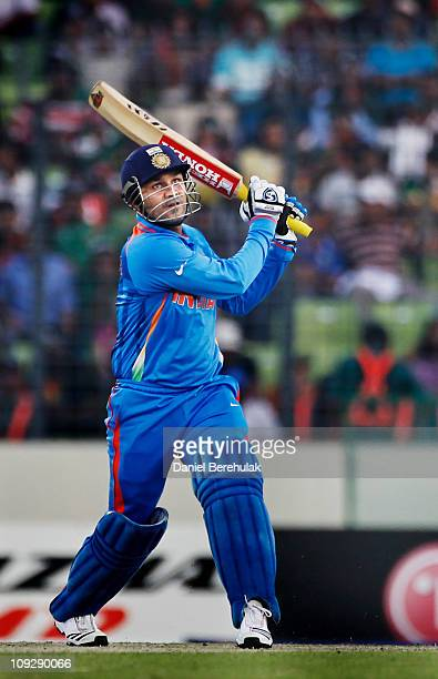 Virender Sehwag of India hits a six during the opening game of the ICC Cricket World Cup between Bangladesh and India at the ShereeBangla National...