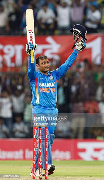 Virender Sehwag of India raises his bat and helmet after scoring a double hundred during the 4th One Day International between India and West Indies...