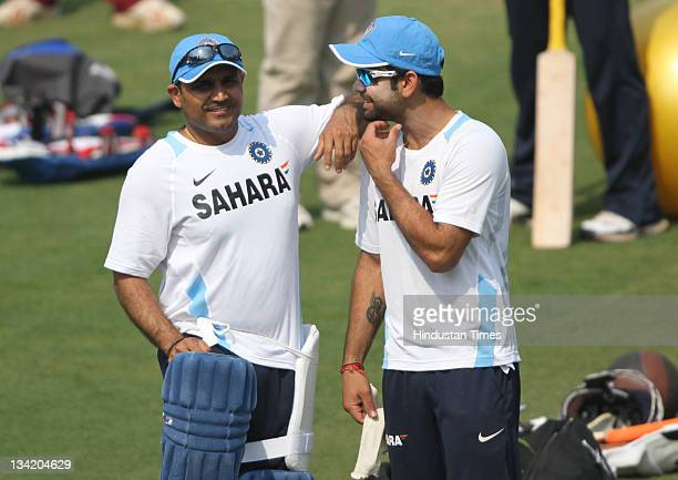 Virendra Sehwag and Virat Kohli of India share a light moment during India's practice session at Barabati Stadium on November 28 2011in Cuttack India